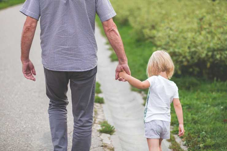 Adult and child holding hands while walking.