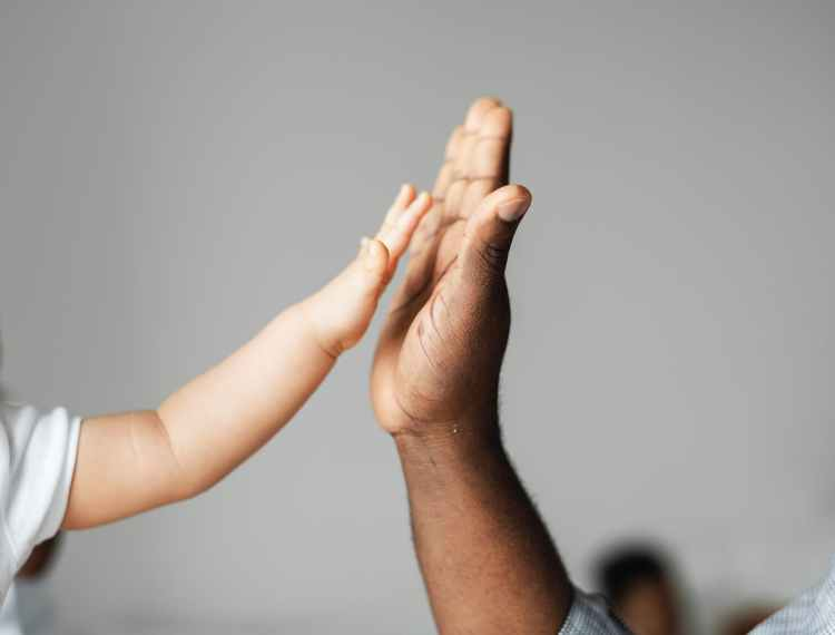 """Adult and child hands about to do a """"high five""""."""